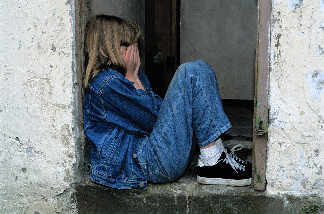 child sitting, jeans, in the door